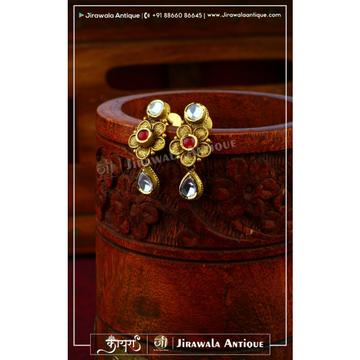 Antique gold jadtar flower shape earring with ruby and white kundan work.